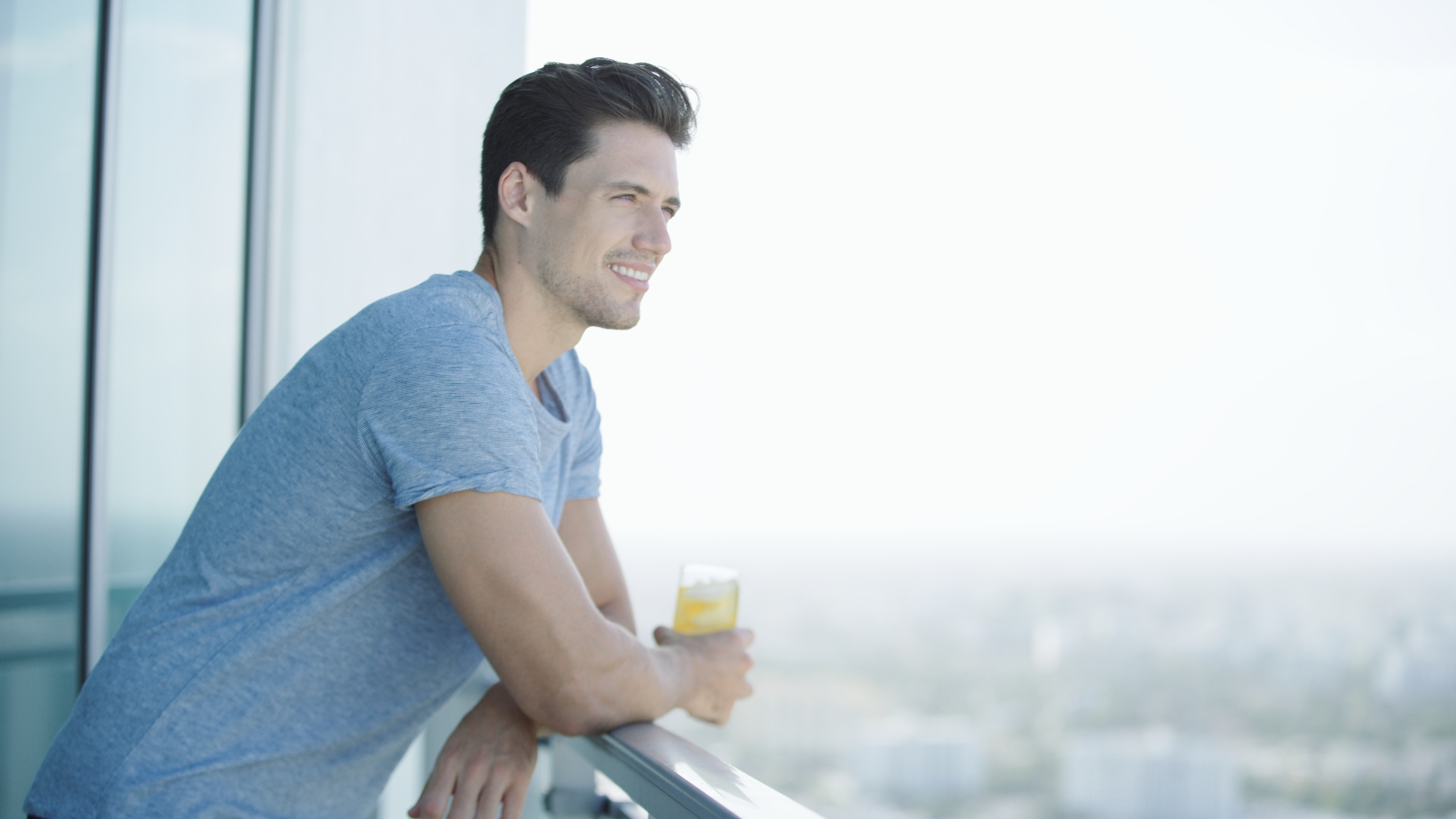Smiling Man Looks Over The City Holding A Cup Of Wake Me UP - The Best Morning Drink For Metabolism