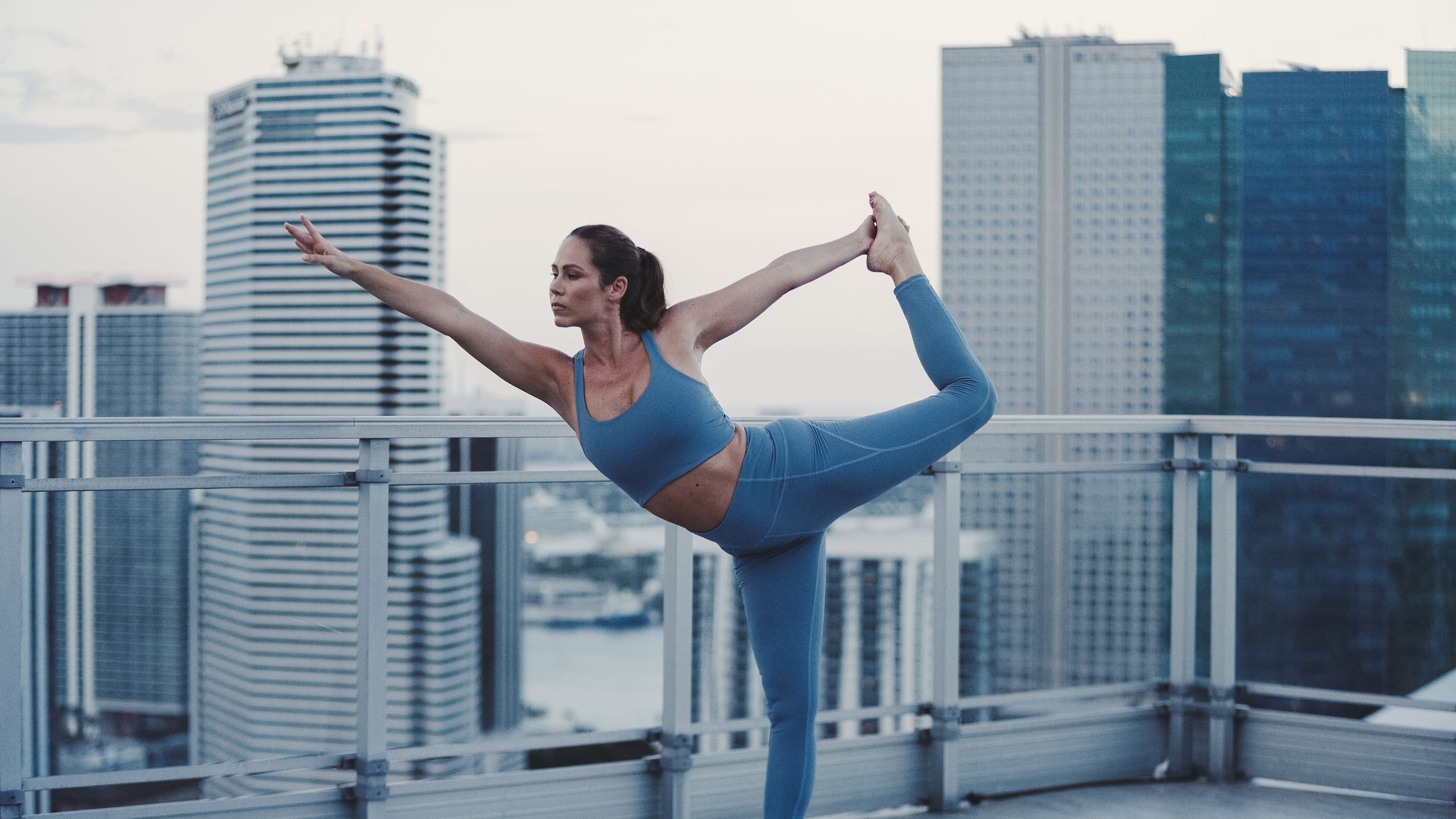 Woman Doing Yoga With City Backdrop