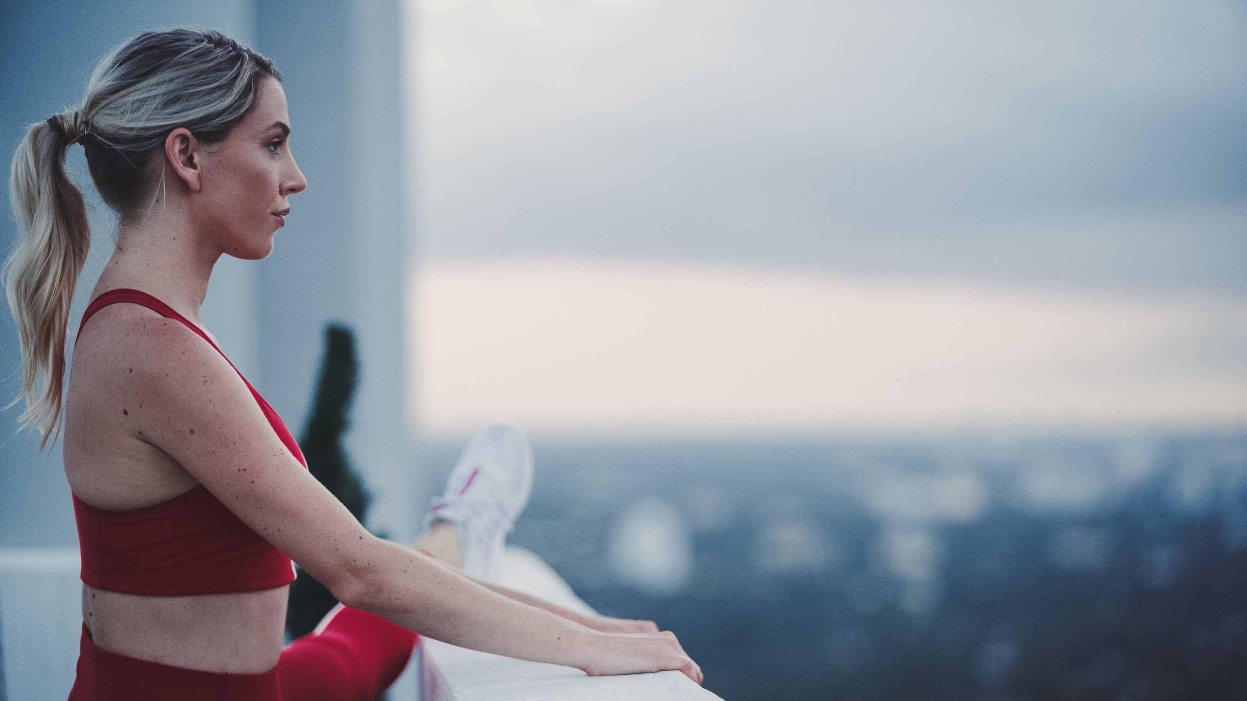 Woman In Red Yoga Clothing Stretches Her Leg And Looks Over The City.