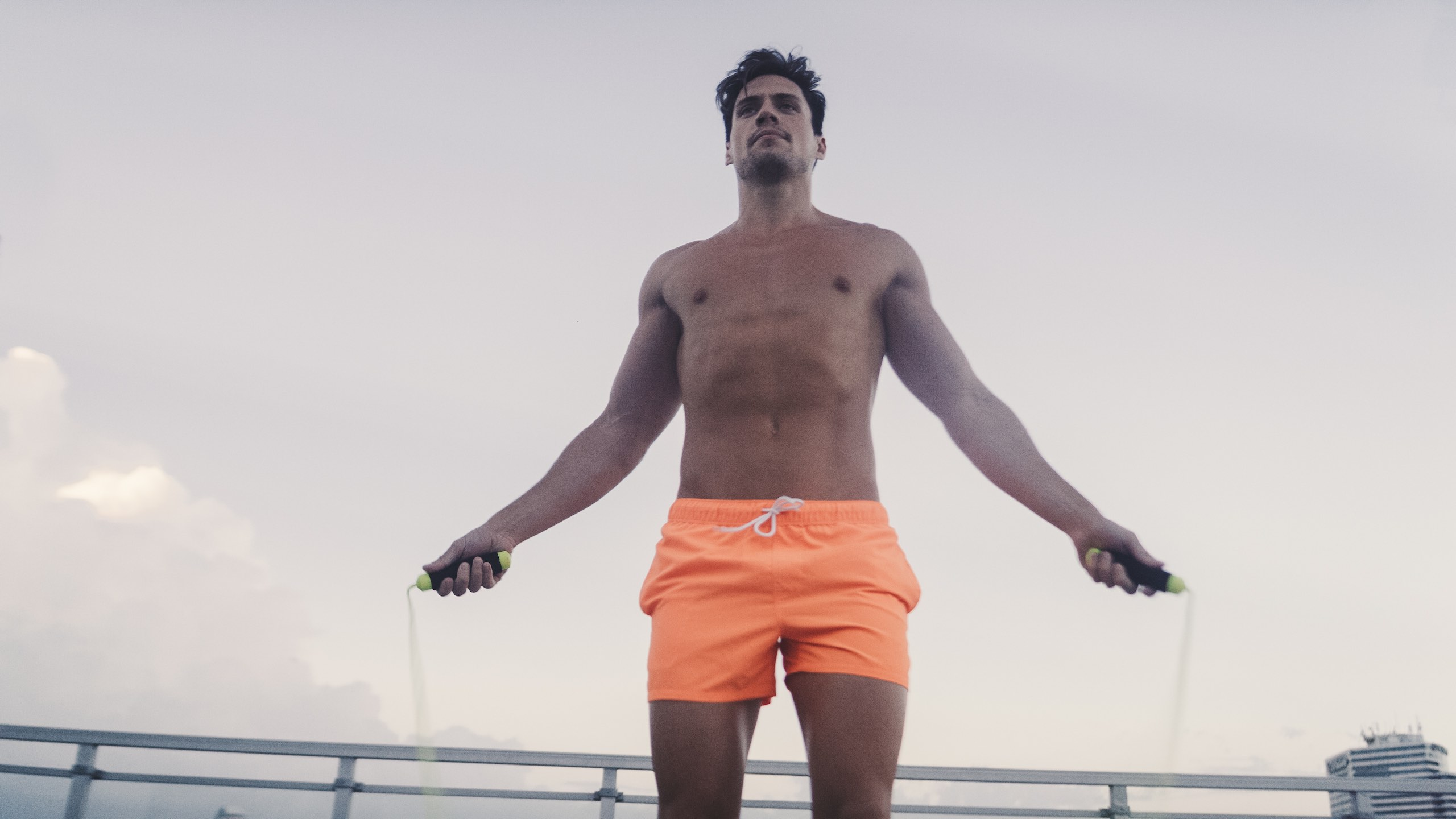 A Man In Orange Shorts Exercises With A Jump Rope Showing Extra Morning Energy.