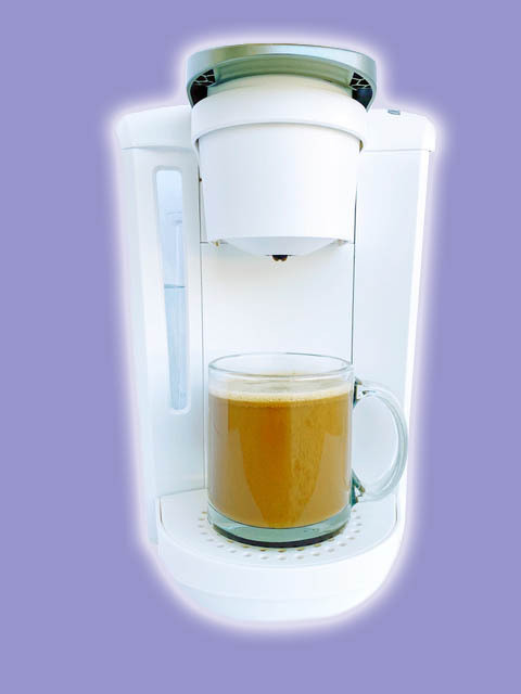 A close-up image of a coffee maker brewing coffee for keto with purple background