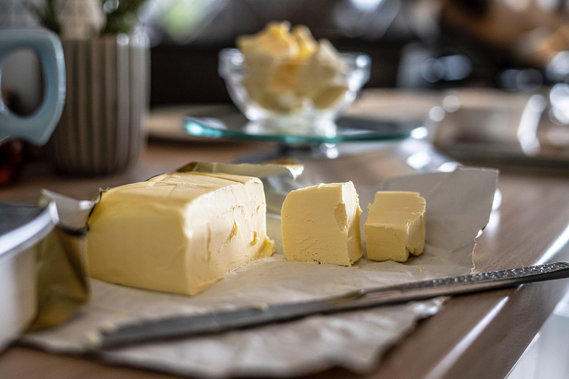 A close-up image of cubed grass-fed butter in its wrappings beside a butterknife on a table