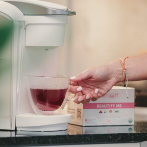 A woman's hand brewing a berry-colored, anti-inflammatory tea from WellOff
