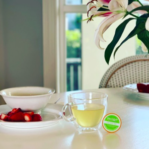 A healthy tea alternative from WellOff sitting on a table beside a bowl and plate of strawberries