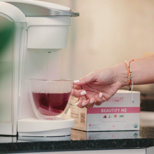 A woman holding a glass mug under a stream of water from a Keurig machine beside a box of tea pods from WellOff