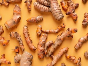 Turmeric roots on an orange backdrop that could be used to make turmeric tea for weight loss