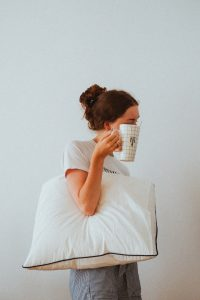 A woman holding a pillow and cup of lavender tea