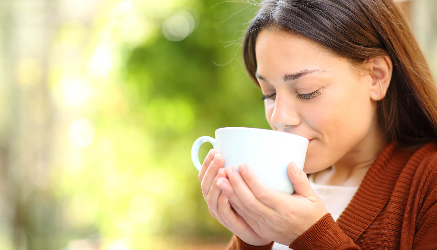 A Woman Sipping A Healthy Hot Drink From A White Cup